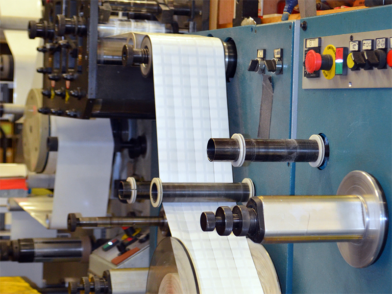 Rotary die cut machine shows the ability to slit die cut adhesive dash pieces in roll form.