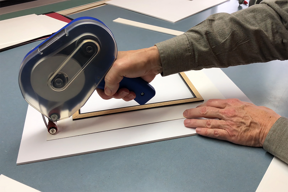 Adhering Pro® 410 ATG to the back of a mat board to apply foam core to level the back of mat surface.