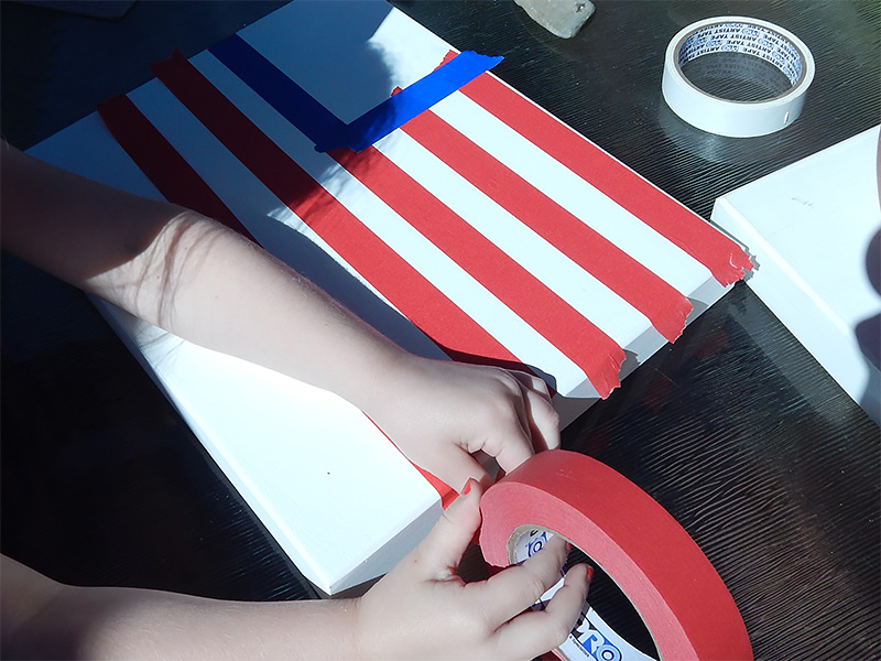 Start by placing the red stripes using Pro® 46 Colored Crepe Masking Tape in Red.