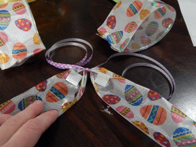 Find the center of the longer piece and tie on some curly ribbon (this is how you will attach the bow to your package). Add a UGlu® Dash to the base of each tail of the ribbon.