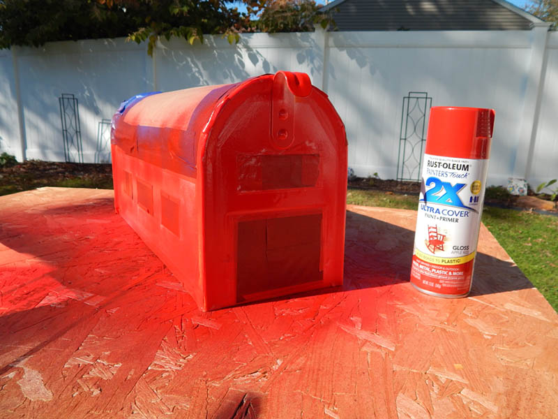 Spray painting the mailbox after masking with tape
