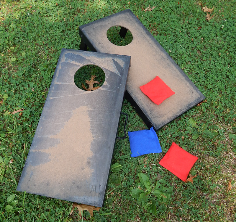 Two unfinished cornhole boards Becky found at a garage sale. She sanded them to down to prepare them for spray painting, but...