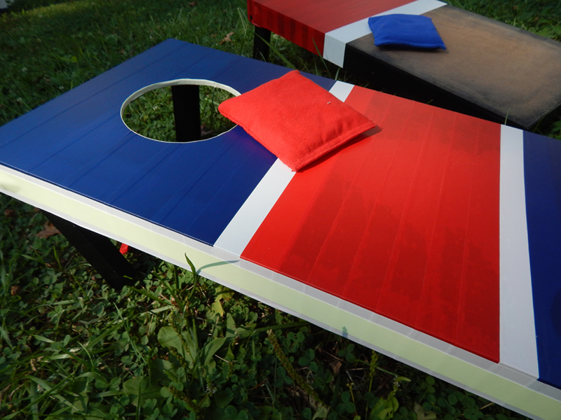 The cornhole game boards and a bean bag, after the boards have been decorated with Pro Splice tape