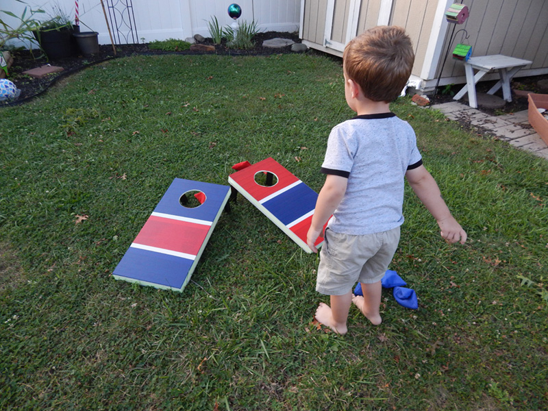 Becky's young son playing with the finished cornhole game boards.