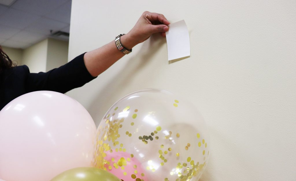 Sticking a UGlu® Power Patch to a wall to hold up balloons