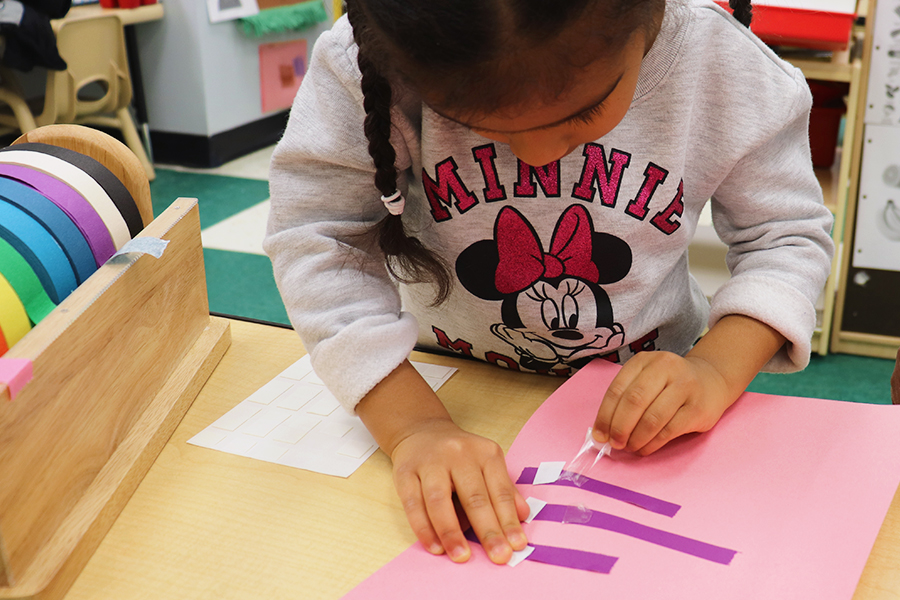 Developing fine motor skills by peeling and sticking tape.